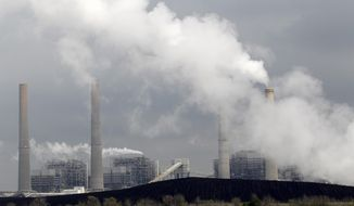 In this March 16, 2011, file photo, exhaust rises from smokestacks in front of piles of coal in Thompsons, Texas.  (AP Photo/David J. Phillip, File) **FILE**