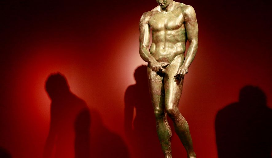 """In this Monday, July 27, 2015 photo, a sculpture titled """"Athlete, The Croatian Apoxyomenos, Greek, 1st century BC,"""" is seen at the J. Paul Getty Museum in the """"Power and Pathos: Bronze Sculpture of Hellenistic World"""" exhibit in Los Angeles. The exhibit brings together more than 50 bronzes from the Hellenistic period that extended from about 323 to 31 B.C. (AP Photo/Nick Ut)"""