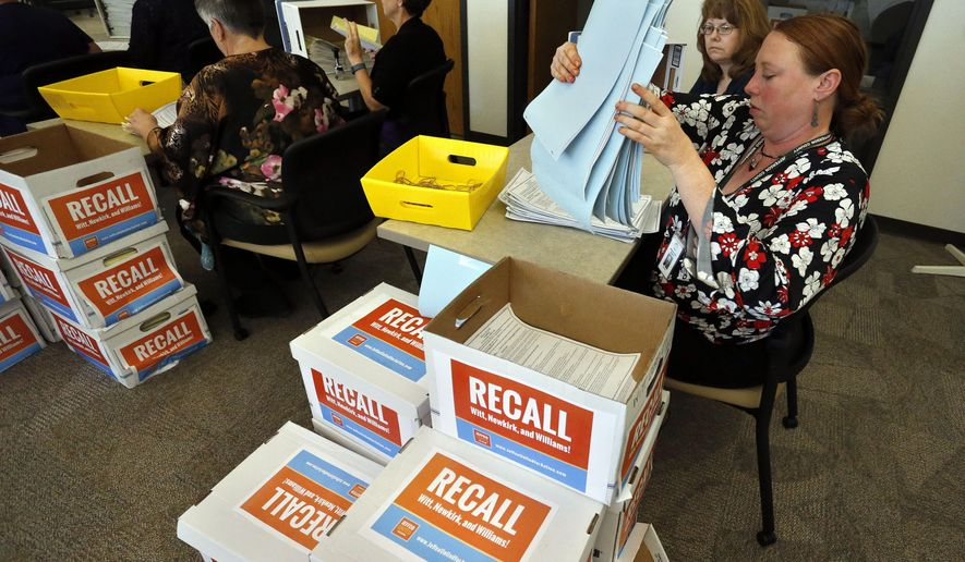 Jefferson County election staffers Sharona Thompson, far right,  and Joy Tirrell, second from right, count and stamp petitions collected by a group of parents and educators, called Jeffco United for Action, whose aim is to remove Jefferson County School Board members Ken Witt, John Newkirk, and Julie Williams, inside the Jefferson County Clerk's Office, in Golden, Colo., Tuesday, July 28, 2015. Critics of the suburban Denver school board that pushed for reviewing class curriculum to emphasize patriotism and downplay civil unrest in the teaching of U.S. history are turning in signatures to force a recall election for the three conservative members responsible for the effort. (AP Photo/Brennan Linsley)