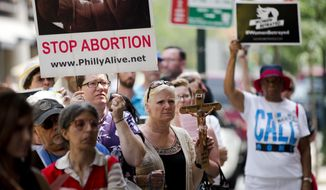Anti-abortion activists demonstrate near a Planned Parenthood clinic Tuesday, July 28, 2015, in Philadelphia. The protesters are calling for an end to government funding for the nonprofit reproductive services organization. (AP Photo/Matt Rourke) ** FILE **