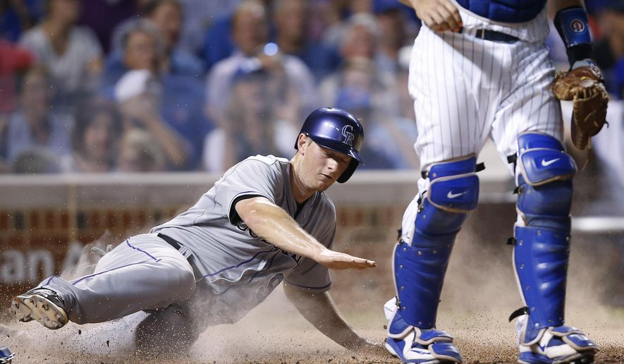 Colorado Rockies' DJ LeMahieu scores past Chicago Cubs catcher Kyle Schwarber as Corey Dickerson grounds out to first during the fifth inning of a baseball game in Chicago, Tuesday, July 28, 2015. (AP Photo/Andrew A. Nelles)