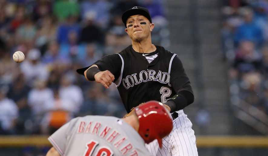 Colorado Rockies shortstop Troy Tulowitzki (2) forces out Cincinnati Reds' Tucker Barnhart (16) at second while throwing out Billy Hamilton at first to complete the double play during the third inning of a baseball game, Friday, July 24, 2015, in Denver. (AP Photo/Jack Dempsey)
