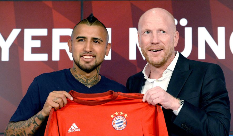 New  player for Bayern Munich , Chile's  Arturo Vidal, left,  and Munich's sports manager Matthias Sammer, right hold a Bayern shirt  after a news conference in Munich, Germany, Tuesday July 28, 2015. Bayern Munich completed the long-anticipated transfer of Chile midfielder Arturo Vidal from Italian champion Juventus on Tuesday. The Bundesliga soccer  champion did not give any immediate details, but German media say Vidal signed a deal through 2020.  (Sven Hoppe/dpa via AP)