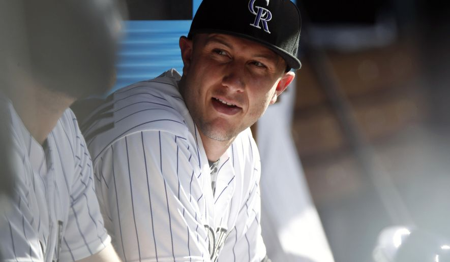 In this photograph taken Sunday, July 26, 2015, Colorado Rockies shortstop Troy Tulowitzki looks on against the Cincinnati Reds in the seventh inning of a baseball game in Denver. Tulowitzki was traded along with relief pitcher LaTroy Hawkins to the Toronto Blue Jays for four players on Tuesday, July 28, 2015. (AP Photo/David Zalubowski)