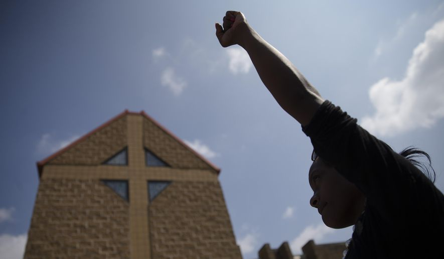 Mourner JeRee Wilson holds her fist in the air outside funeral services for Samuel Dubose at the Church of the Living God in the Avondale neighborhood of Cincinnati, Tuesday, July 28, 2015. Dubose was fatally shot by a University of Cincinnati police officer who stopped him for a missing license plate. (AP Photo/John Minchillo)
