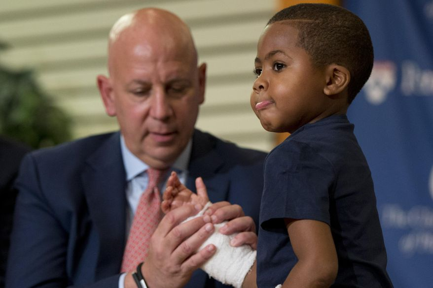 As Dr. L. Scott Levin holds his hand, double-hand transplant recipient 8-year-old Zion Harvey moves his fingers during a news conference Tuesday, July 28, 2015, at The Children's Hospital of Philadelphia (CHOP) in Philadelphia.  Surgeons said Harvey of Baltimore who lost his limbs to a serious infection,  has become the youngest patient to receive a double-hand transplant. (AP Photo/Matt Rourke)