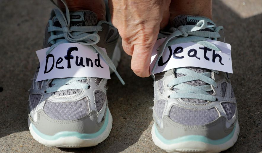 Kathy Calver adjusted signs on her shoes as she and other pro-life activists rallied at the Texas Capitol, under the banner of #WomenBetrayed, to condemn the use in medical research of tissue samples obtained from aborted fetuses.