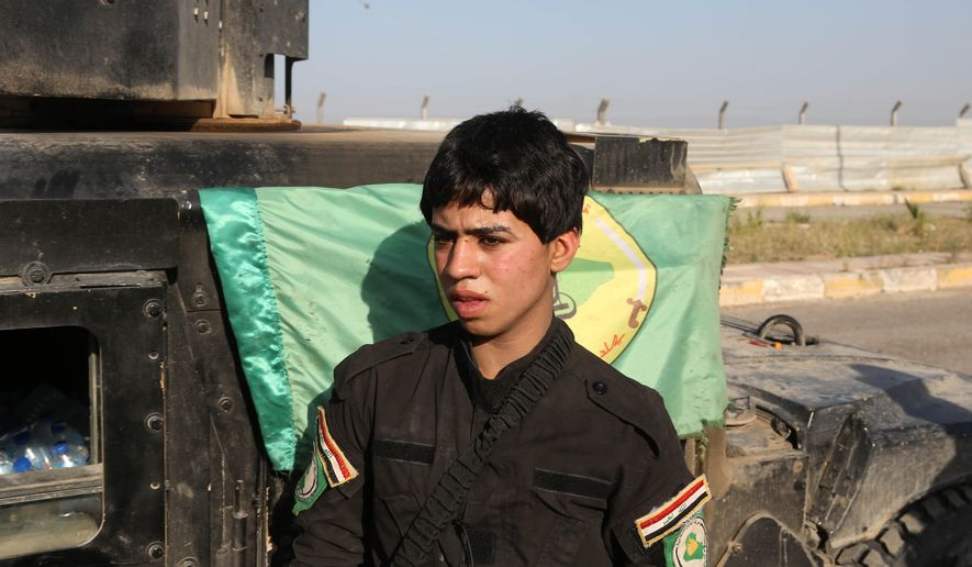 FILE - In this Sunday, March 15, 2015, file photo, a young Shiite volunteer militiaman stands near a vehicle on his way to the battlefield against Islamic State fighters in Tikrit, Iraq. The Associated Press has found that militia forces battling the Islamic State group are actively training children under 18 years old. (AP Photo/Khalid Mohammed, File)