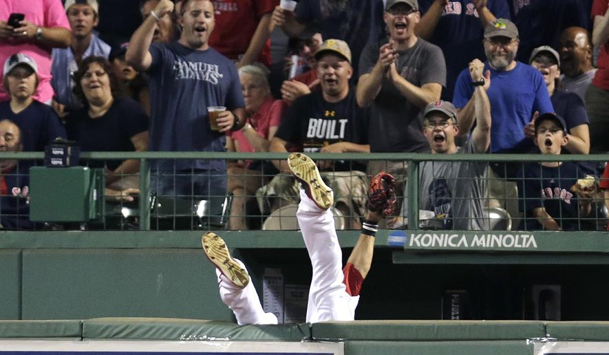 Boston Red Sox center fielder Mookie Betts flips over the bullpen wall while trying to field a drive by Chicago White Sox's Jose Abreu during the sixth inning of a baseball game at Fenway Park in Boston, Tuesday, July 28, 2015. Umpires ruled the play a home run after video replay review. (AP Photo/Charles Krupa)