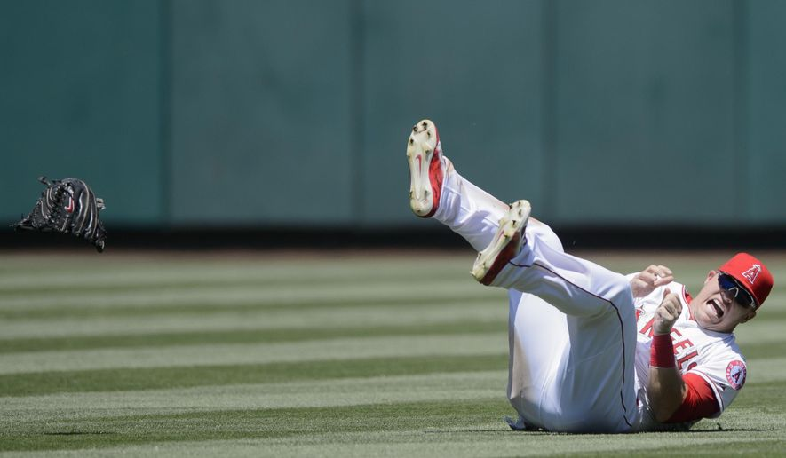 Los Angeles Angels center fielder Mike Trout reacts after landing on his hand as he attempted to catch a fly ball hit by Texas Rangers' Elvis Andrus during the fourth inning of a baseball game in Anaheim, Calif., Sunday, July 26, 2015. (AP Photo/Kelvin Kuo)