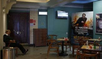A woman sits at a restaurant in the eastern Russian city of Vladivostok on Sept. 10, 2012. (Associated Press) **FILE**