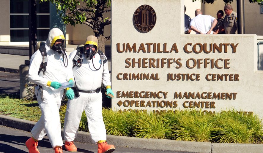 On Monday, July 27, 2015, Hermiston firefighters in hazmat suits carry what was reported as a suspicious letter from a car at the Umatilla County Sheriff's Office, in Pendleton. Ore. The FBI says no toxic substances have been found in letters sent to about 20 Oregon sheriffs or their offices.  The FBI said Tuesday that none of the envelopes contained a visible powder, contradicting earlier reports. Sheriffs around the state have reported receiving envelopes with rambling, incoherent messages. /East Oregonian via AP) MANDATORY CREDIT (REV-SHARE)