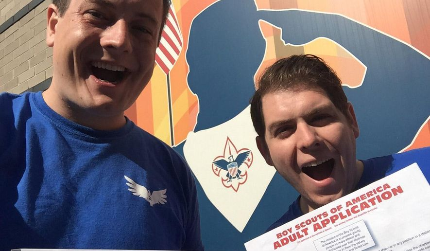 In this Tuesday, July 28, 2015, photo, Eric Hetland (left) and Chris Zelis, who are with Scouts For Equality in Chicago, hold up their applications for assistant scoutmasters before submitting them in the Chicago suburb of Oak Park. Mr. Hetland, who works at a high school science academy, had been involved in scouting from age 5 to 22, when he came out as bisexual and was not asked back to a job at a Scout summer camp. (Eric Hetland via AP)