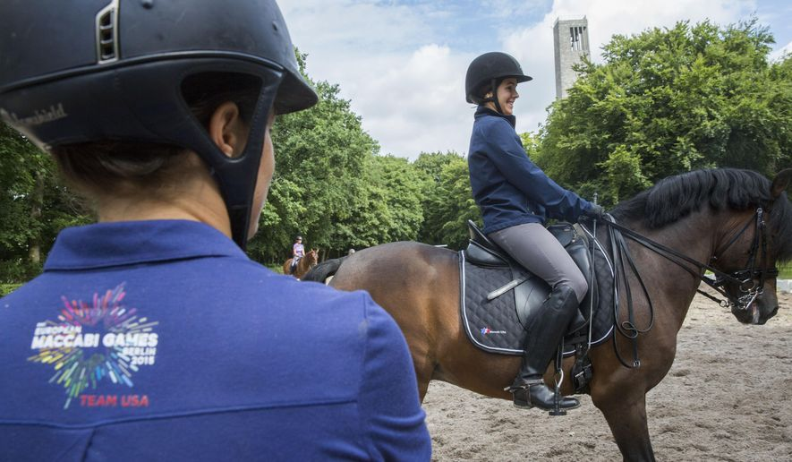 Anna Jaffe, left, from the US  watches her compatriot rider  Katie Resnick  during a dressage training session at the European Maccabi Games in Berlin, Germany, Tuesday, July 28, 2015.  More than 2,000 Jewish athletes are gathering in Berlin for the European Maccabi Games, being held for the first time in Germany, and  at sites constructed by the Nazis for the 1936 Olympics.   (AP Photo/Gero Breloer)