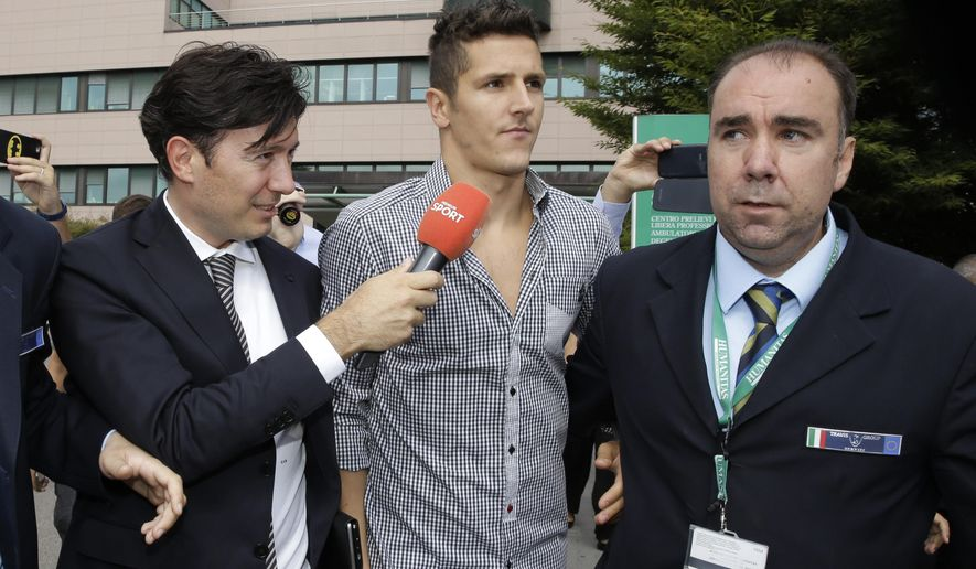 Manchester City forward  Stevan Jovetic, center,  leaves the hospital after a medical examination for Inter Milan Serie A soccer team in Rozzano near Milan, Italy, Tuesday, July 28 , 2015. (AP Photo/Luca Bruno)