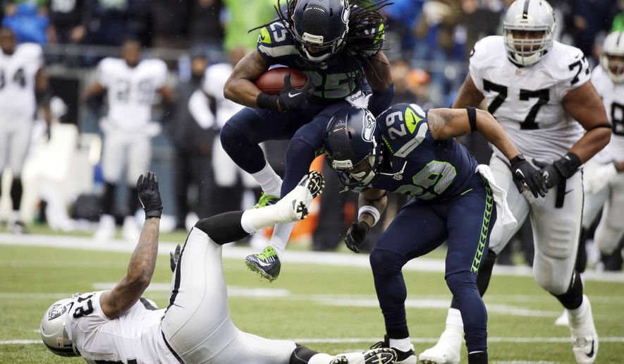 File - In this Nov. 2, 2014, file photo, Seattle Seahawks cornerback Richard Sherman jumps over Oakland Raiders' tight end Mychal Rivera, left, and Seahawks' Earl Thomas (29) after making an interception in the first half of an NFL football game in Seattle. (AP Photo/Elaine Thompson, File)