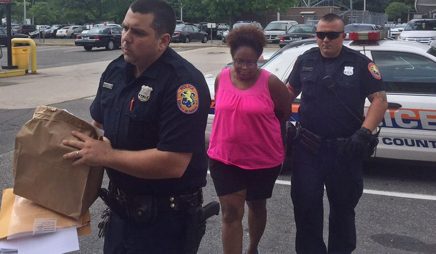 Yolanda Gilreath, 51, center, is escorted into the Nassau County police headquarters in Mineola N.Y., Tuesday, July 28, 2015, after she and her son Malachi Blaylock, 20,  were arrested on charges they kidnapped Blaylock's former girlfriend and their baby and kept them captive for several days on Long Island. Police said the 20-year-old woman was lured by a text message from Gilreath, the child's grandmother, saying she wanted to see the child. When the woman arrived, police said Blaylock grabbed the child and kept the woman captive, and beat her repeatedly for five days, until she was able to call for help.  (AP Photo/Mike Balsamo)