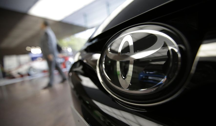 FILE - In this May 8, 2015 file photo, Toyota logo on a car is seen at Toyota's headquarters building in Tokyo. Japanese automaker Toyota Motor Corp. said Tuesday, July 28, 2015 it sold 5.02 million vehicles in the first six months of this year, down 1.5 percent from the same period the previous year, as sales struggled especially in the languishing Japanese market. Volkswagen overtook Toyota in global vehicle sales for January-June, the first time the German automaker has come out top in the intensely competitive tallies. (AP Photo/Eugene Hoshiko, File)