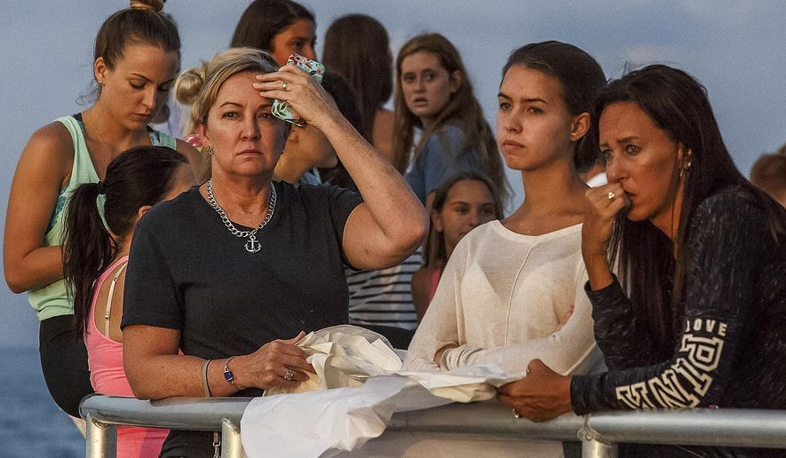 People gather during a candlelight vigil and paper balloon release at Jupiter Inlet Park, Monday, July 27, 2015, for teenagers Austin Stephanos and Perry Cohen in Jupiter, Fla. The teens were last seen Friday afternoon buying fuel near Jupiter and were believed to have been heading toward the Bahamas. (Thomas Cordy/The Palm Beach Post via AP)