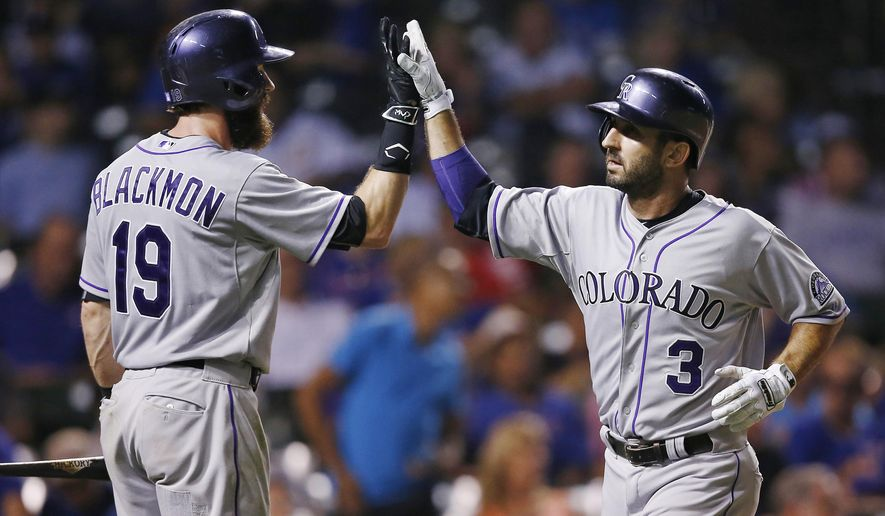 Colorado Rockies' Daniel Descalso, right, celebrates his solo home run with teammate Charlie Blackmon during the ninth inning of a baseball game against the Chicago Cubs in Chicago, Monday, July 27, 2015. (AP Photo/Andrew A. Nelles)
