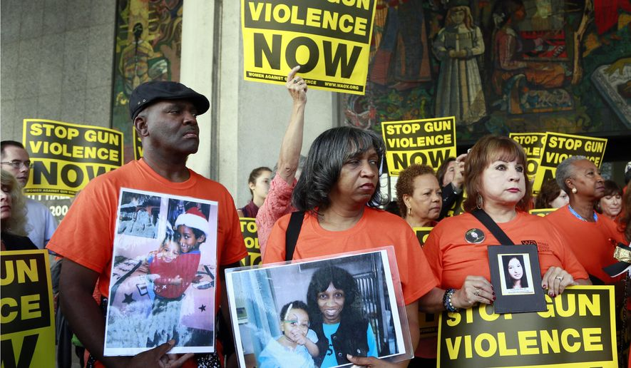 Parents of victims of gun violence, pastor Ruett Foster, from left, his wife Rhonda and Anna Del Rio hold pictures of their late children, during a rally supporting a city ordinance to ban the possession of high-capacity gun magazines outside Los Angeles City Hall, Tuesday, July 28, 2015. The Los Angeles City Council has voted to ban possession of high-capacity gun magazines in the wake of several deadly mass shootings around the country. (AP Photo/Nick Ut)