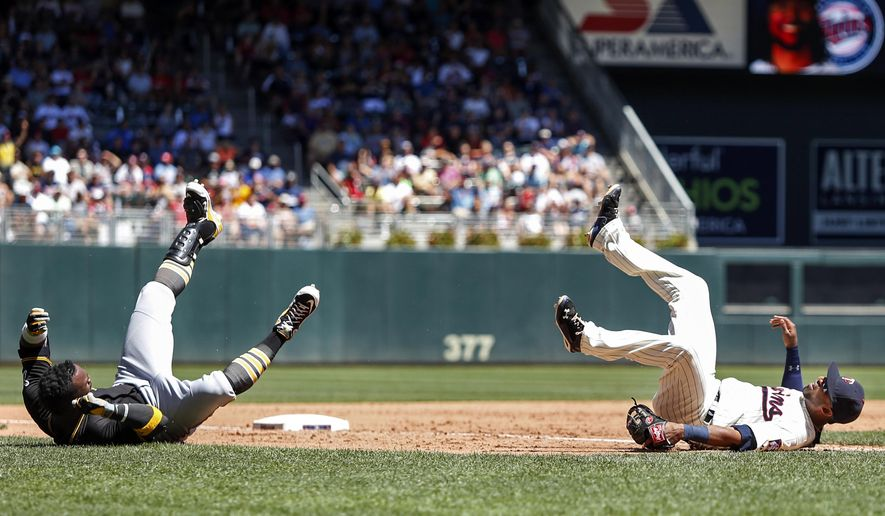 Pittsburgh Pirates' Andrew McCutchen, left, and Minnesota Twins third baseman Eduardo Nunez, right, roll after colliding on a four-run single by McCutchen in the sixth inning of a baseball game Wednesday, July 29, 2015, in Minneapolis. The Pirates won 10-4. (AP Photo/Bruce Kluckhohn)