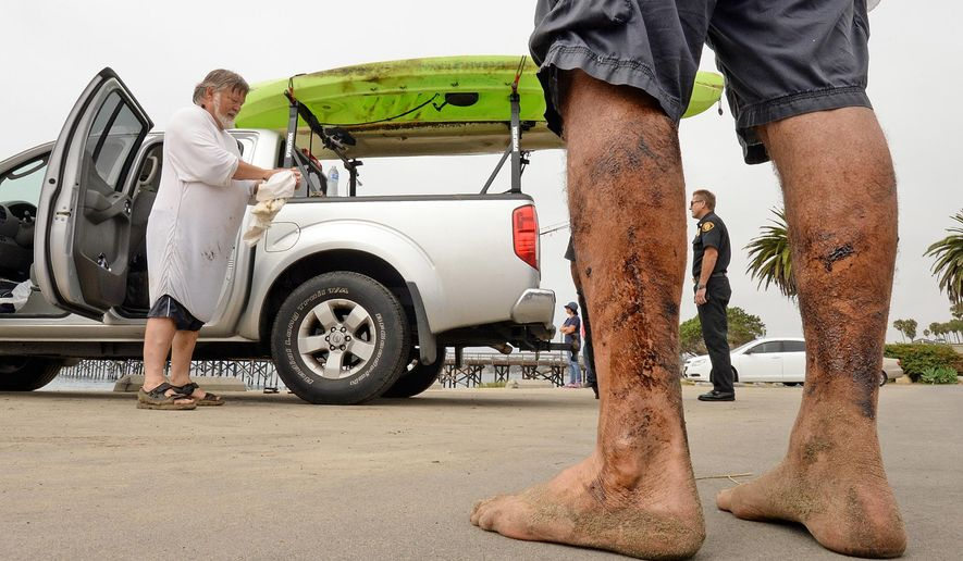 In this photo provided by the Santa Barbara County, Calif., Fire Department, Henry Duncan, left, and Bob Seiler, legs covered in oil, foreground, stand in the Goleta Beach parking lot with their oil-covered kayaks, on the truck at rear, in Goleta, Calif., Wednesday, July 29, 2015.  The pair encountered a large oil sheen and called the fire department to investigate. The Coast Guard is investigating this new oil slick off the Southern California coast about a dozen miles from where a broken pipeline spilled thousands of gallons of crude into the ocean in May.   (Mike Eliason/ Santa Barbara County Fire Department via AP)