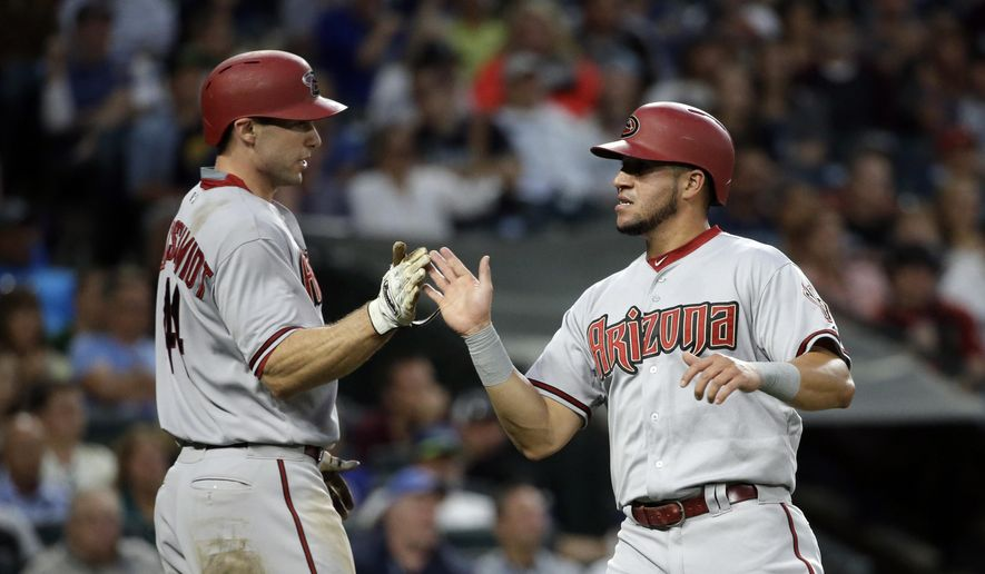Arizona Diamondbacks' Paul Goldschmidt, left, greets David Peralta as the two score on a single by Chris Owings against the Seattle Mariners in the sixth inning of a baseball game, Tuesday, July 28, 2015, in Seattle. (AP Photo/Elaine Thompson)