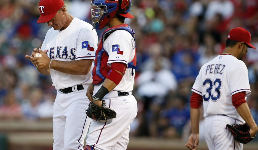 Texas Rangers manager Jeff Banister, left, stands on the mound with catcher Robinson Chirinos after taking the ball from starter Martin Perez (33) in the second inning of a baseball game against the New York Yankees, Tuesday, July 28, 2015, in Arlington, Texas. (AP Photo/Tony Gutierrez)