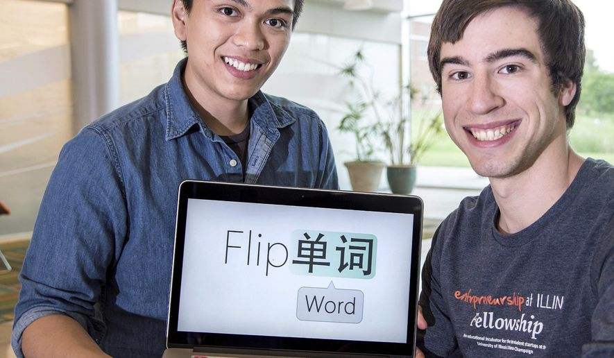 In this photo taken, June 19, 2015, Joseph Milla, left, and Thomas Reece hold up a laptop displaying their web application called FlipWord, at the University of Illinois Research Park in Champaign, Ill. FlipWord is an application that allows users to browse a website while passively being exposed to words in another language. (Heather Coit/The News-Gazette via AP) MANDATORY CREDIT