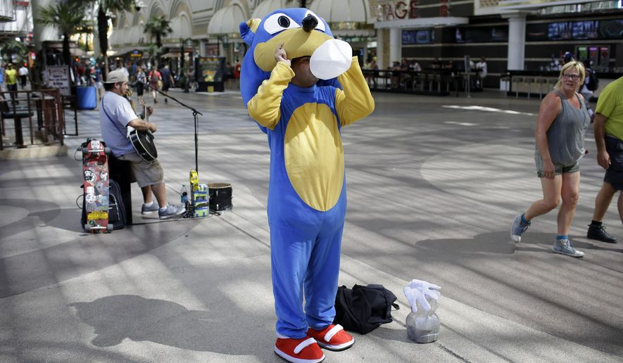 FILE - In this July 24, 2014 file photo, street performer Daniel Gallegos drinks water while the temperature remain in the triple digits in Las Vegas.   Las Vegas city officials announced a proposed ordinance establishing specific zones where 27 to 38 tip-seeking performers can entertain between 3 p.m. and 2 a.m. under Fremont Street's massive video-screen awning. Entertainers will also need to register with the city. (AP Photo/John Locher)