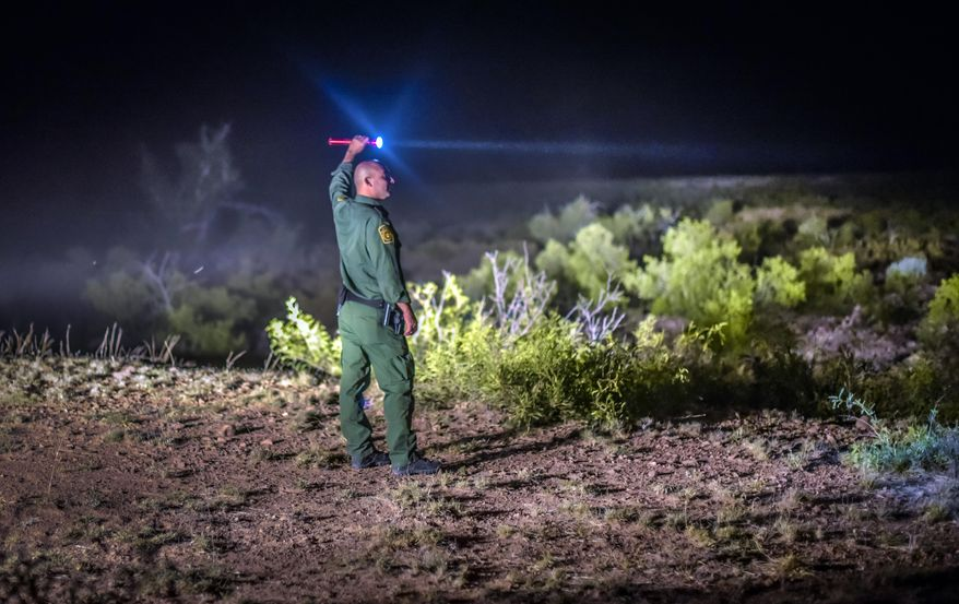 This photo taken June 24, 2015, shows a Border Patrol  agent looking for other agents escorting six undocumented immigrants that were apprehended in the Animas mountains in New Mexico's boot heel. (Roberto E. Rosales/The Albuquerque Journal via AP)