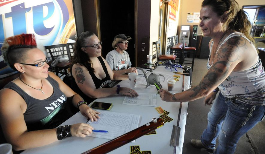 Amy Hawes signs a marijuana petition from Reina Parker, Kim Shelton and Jon Gilles at Big's Sports Bar in Sioux Falls, S.D. Wednesday, July 29, 2015. South Dakotans Against Prohibition officially kicked off its campaign to put a measure on the November ballot in 2016 that would ask voters whether the state should decriminalize marijuana. (Emily Spartz Weerheim/Argus Leader via AP) NO SALES
