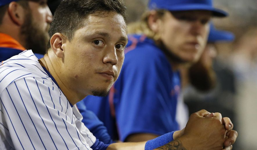New York Mets' Wilmer Flores, foreground, sits in the dugout during a baseball game against the San Diego Padres in New York, Wednesday, July 29, 2015. (AP Photo/Kathy Willens)