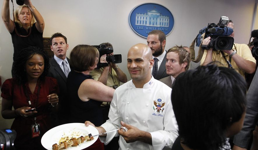 """In this Monday, Aug. 9, 2010 photo, White House assistant chef Sam Kass serves members of the media Gulf shrimp grilled by the 2009 NFL Super Bowl Football Champions New Orleans Saints in the White House briefing room of the White House in Washington. On Wednesday, July 29, 2015, NBC News announced that Kass, who worked at the White House from 2009 until 2014, would serve as a senior food analyst for """"Today"""" and """"NBC Nightly News with Lester Holt,"""" as well as write a monthly online column for Today Food. (AP Photo/Charles Dharapak)"""