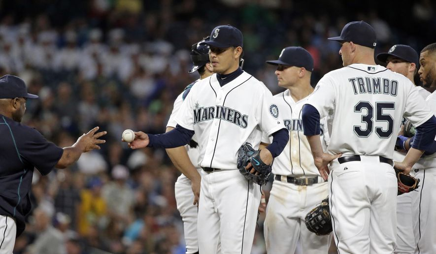 Seattle Mariners manager Lloyd McClendon, left, reaches for the game ball from starting pitcher Hisashi Iwakuma as he pulls Iwakuma against the Arizona Diamondbacks in the sixth inning of a baseball game, Tuesday, July 28, 2015, in Seattle. (AP Photo/Elaine Thompson)