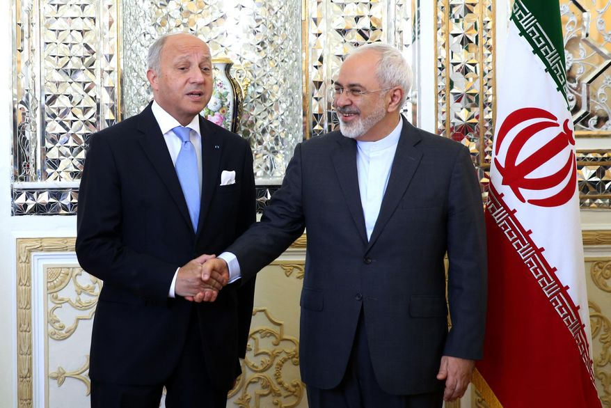 "Iranian Foreign Minister Mohammad Javad Zarif, right, and his French counterpart Laurent Fabius shake hands for media prior to their round of talks in Tehran, Iran, Wednesday, July 29, 2015. Iran's state media say French Foreign Minister Laurent Fabius's visit to Iran is the start of a 'new era' in bilateral relations following a historic nuclear deal with world powers earlier this month. Fabius said Wednesday the time has come for Iran and France to warm up their relations, calling his visit ""an important trip.""(AP Photo/Ebrahim Noroozi)"