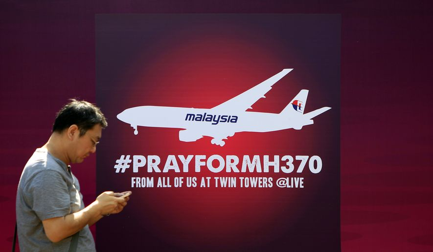 "A man walks past a board reading ""Pray for MH370"" in Kuala Lumpur, Malaysia, on March 15, 2014. (Associated Press)"
