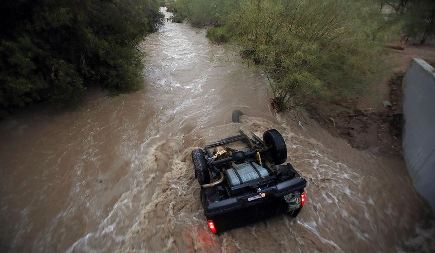 Water rushes around a vehicle near S. Elizabeth Drive and W. Lincoln Street after a storm, Tuesday, July 28, 2015, in Tucson, Ariz. The occupants of the vehicle made it out safely. (Mamta Popat/Arizona Daily Star via AP)