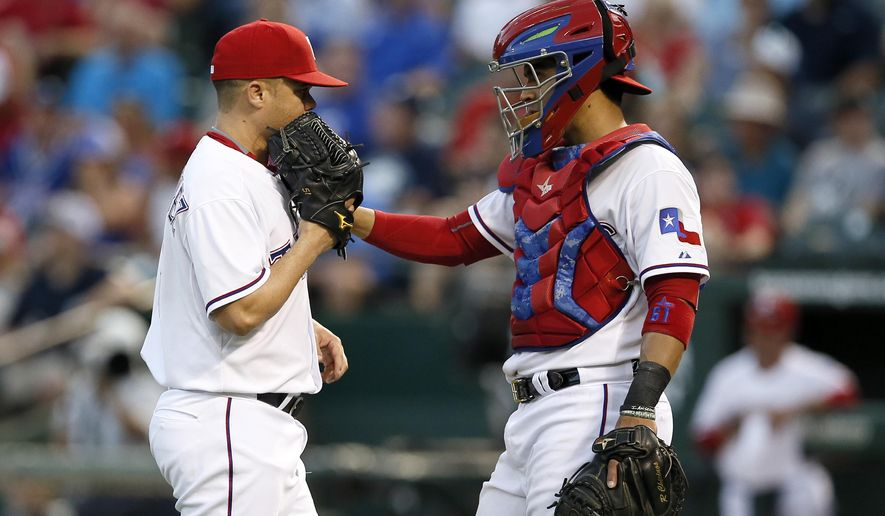 Texas Rangers relief pitcher Wandy Rodriguez talks with catcher Robinson Chirinos, right, in the second inning of a baseball game against the New York Yankees, Tuesday, July 28, 2015, in Arlington, Texas. (AP Photo/Tony Gutierrez)