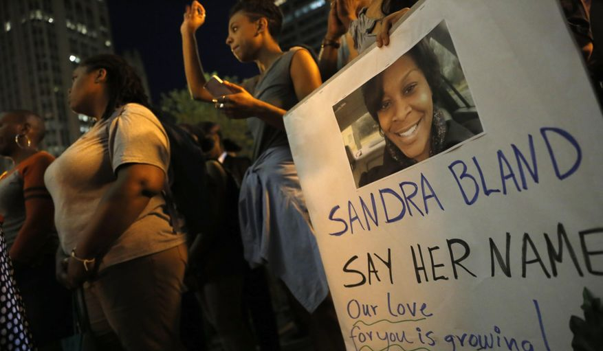 A demonstrator holds a Sandra Bland sign during a vigil, Tuesday evening, July 28, 2015,  near the DuSable Bridge on Michigan Ave. in Chicago. Bland died in a Texas county jail after the traffic stop for failing to use a turn signal escalated into a physical confrontation. Authorities have said Bland hanged herself, a finding her family disputes. The death has garnered national attention amid increased scrutiny of police treatment of blacks in the wake of several high-profile police-involved deaths. (AP Photo/Christian K. Lee) ** FILE **