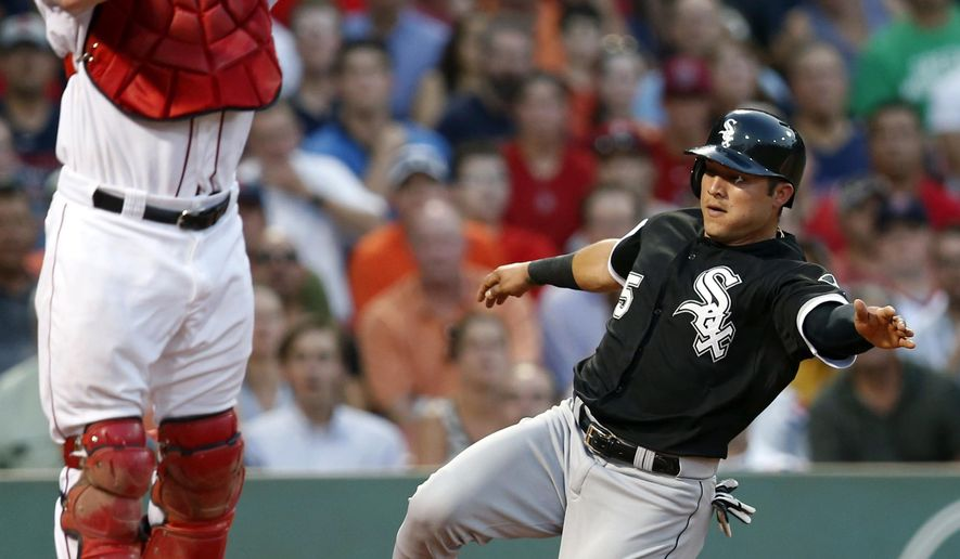 Chicago White Sox's Carlos Sanchez (5) scores on a single by Adam Eaton as Boston Red Sox's Ryan Hanigan jumps for the high throw during the second inning of a baseball game in Boston, Wednesday, July 29, 2015. (AP Photo/Michael Dwyer)
