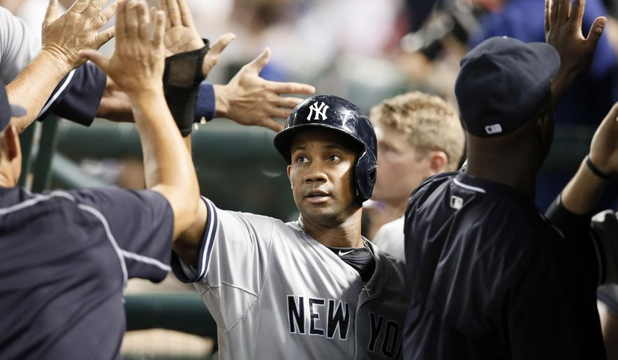 New York Yankees' Chris Young is congratulated in the dugout after he and Garrett Jones scored on a John Ryan Murphy single in the sixth inning of a baseball game against the Texas Rangers Tuesday, July 28, 2015, in Arlington, Texas. (AP Photo/Tony Gutierrez)