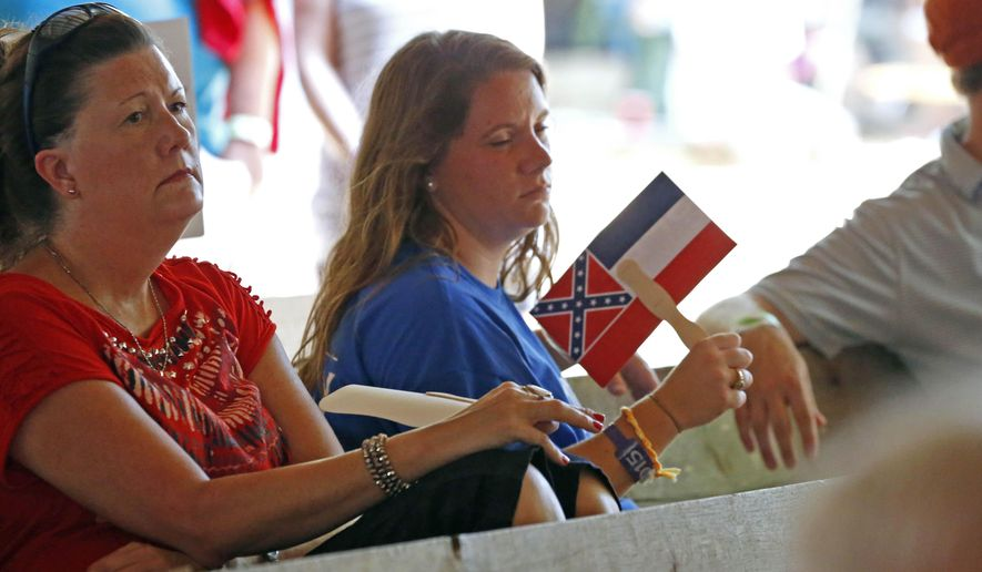 A person uses a Mississippi state flag campaign hand fan at the Neshoba County Fair, Wednesday, July 29, 2015, in Philadelphia, Miss. The fair is a traditional gathering place for politicians, area residents, business leaders, voters and families. (AP Photo/Rogelio V. Solis)