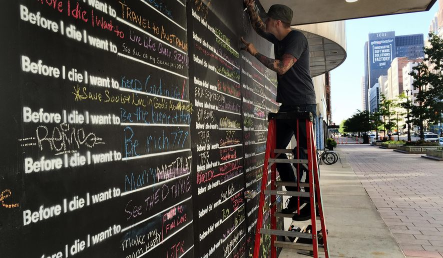 """Artist Mark Serra puts on finishing details """"Before I die I want to"""" project on Monday, July 28, 2015 in Detroit.  The interactive art display offers people a chance to share their life goals. (Robin Erb/Detroit Free Press via AP)  DETROIT NEWS OUT; TV OUT; MAGS OUT; NO SALES; MANDATORY CREDIT DETROIT FREE PRESS"""