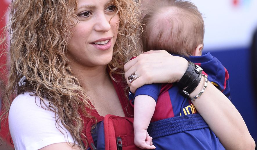"""FILE - In this April 18, 2015 file photo, Colombian singer Shakira holds her son Sasha prior to a Spanish La Liga soccer match between FC Barcelona and Valencia at the Camp Nou stadium in Barcelona, Spain. On Wednesday, July 29, Shakira posted on Twitter and Facebook a video titled """"Happy 6 months Sasha!"""" in which she appears holding Sasha in front of a soccer ball. The child raised his leg and gently kicked the ball. (AP Photo/Manu Fernandez, File)"""