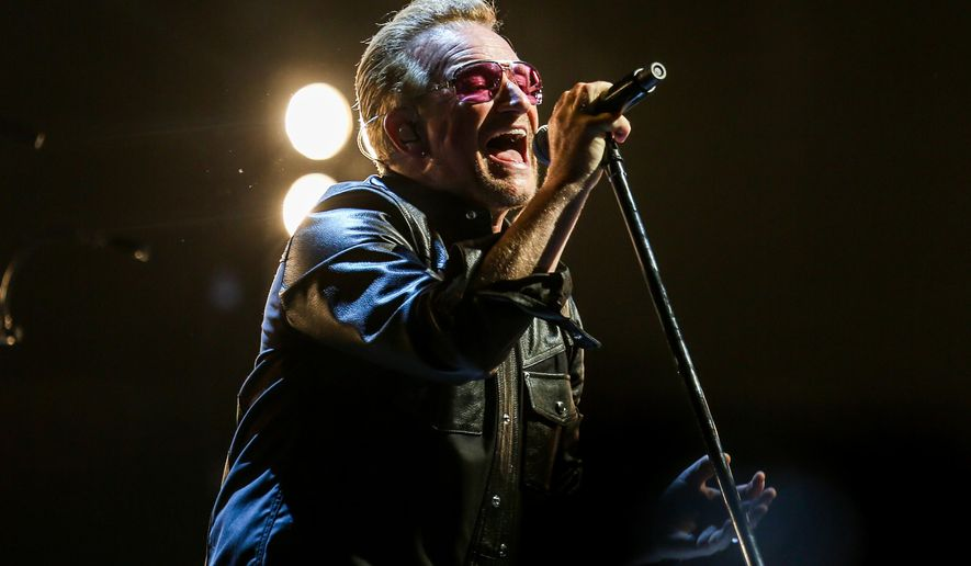 In this May 26, 2015 photo, Bono of U2 performs at the Innocence + Experience Tour at The Forum in Inglewood, Calif. HBO and U2 are collaborating on a double-barreled special about the veteran Irish rock band's current world tour. The network said that it will air a documentary in November about how the show was put together and how the band overcame obstacles, including singer Bono's serious bicycle accident, to perform. U2 is currently on a run of shows in New York. (Photo by Rich Fury/Invision/AP, File)