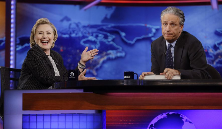 """In this July 15, 2014, file photo, former U.S. Secretary of State Hillary Rodham Clinton reacts to host Jon Stewart during a taping of """"The Daily Show with Jon Stewart,"""" in New York. After more than 16 years and nearly 2,600 telecasts, Stewart ended his show on Aug. 6. (AP Photo/Frank Franklin II, File)"""