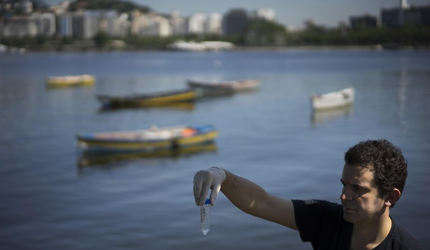 """In this April 28, 2015 photo, Fernando Spilki, virologist and coordinator of the environmental quality program at Feevale University, holds up a water sample, backdropped by the Marina da Gloria, Zone 2, in Rio de Janeiro, Brazil. Spilki said the tests he conducted for the Associated Press so far show that Rio's waters """"are chronically contaminated."""" (AP Photo/Felipe Dana)"""