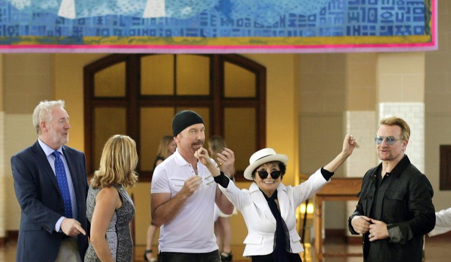 Yoko Ono, widow of John Lennon, second right, reacts after the unveiling of a 24' x 10' tapestry depicting the island of Manhattan as a yellow submarine piloted by a waving John Lennon at Ellis Island Wednesday, July 29, 2015, in New York. Standing with Ono are Bono, right, and The Edge, of the Irish rock band U2, third from right.  (AP Photo/Frank Franklin II)